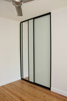 Mode Sliding White Glass doors with black frames.  Is it just me or do these doors look elegant.  The functionality in these doors is great.  There is a mirror in one of the doors and the white glass panel can also be used as a white board.  www.formfunctionnt.com.au Mirror Panels, Glass Panels, White Sliding Wardrobe, Black Frames, Glass Doors, Sliding Doors, Range, Pocket, Living Room