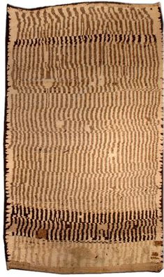 A Moroccan rug BB2829 - A second quarter 20th century Moroccan carpet on a faded camel ground with darker caramel and brown vertical ...