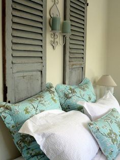 old shutters as headboard ~ candle wall sconce in center ~ lovely bedroom design
