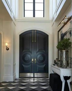 A two story foyer features black arched front doors accented with brass plates alongside a large art piece illuminated by a brass picture light over a Noir Pegas Console, atop a black and white diamond pattern floor in First Snow Elegance Marble, Zebrano Arched Front Door, Black Front Doors, Front Entrances, Double Front Entry Doors, Door Design, House Design, Entry Way Design, Entrance Design, Alice Lane Home