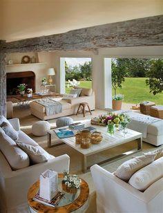 Salón con viga pintada en blanco, chimenea y grandes ventanales que comunican al jardín