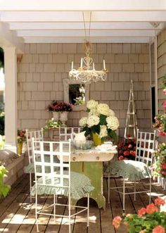 Love this chandelier!  Pots of colorful flowers and a candle chandelier give this porch the look of a garden-themed dining room. Anchoring the arrangement is a vintage green-and-white baker's table. New white metal chairs slide underneath, looking right at home.