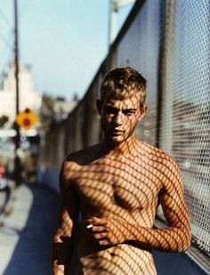 note urban setting, retro colour, and phenomenal shadows sculpting his torso; model: Paul Jasmin