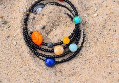 """""""The total number of stars in the Universe is larger than all the grains of sand on all the beaches of planet Earth."""" - Carl Sagan #WednesdayWords #SolarSystemBracelet #CarlSagan #cosmos #astronobeads #spacejewelry #solarsystembracelet #planets #astronomyquote #BiggerThanABracelet"""