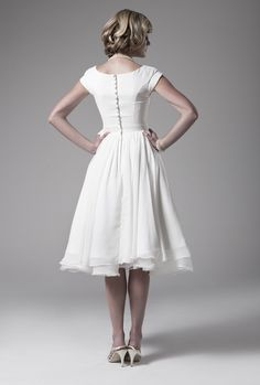 White tea length dress, short cap sleeves, fitted bodice with fabric covered buttons, the skirt has 8 layers of chiffon. To see these skirts sensuously floating around legs would be mesmerizing. The hair style is lovely, modest high heels, nothing has been added to detract the eye from enchanting femininity.