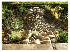 Check dams made from packed earth and river rock are used in each curb extension to slow and retain stormwater runoff. Innovation and Photo Credit: Kevin Robert Perry.