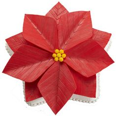 A Perfect Poinsettia Cake - Set your holiday dessert table with the most festive flower of the season. Star cake covered with fondant poinsettia petals. Sure to be the center of attention on your holiday table.