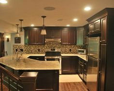 dark cabinets and wood floors. recessed and pendant lighting