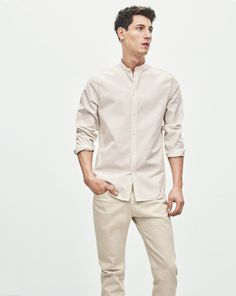 Modern minimalist collarless shirt and raglan cut sleeve. Style it untucked with sleeves folded up in a monochrome fashion for a modern look.