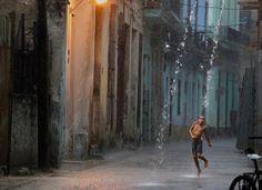 Un niño baila bajo la lluvia en una calle de la Habana Vieja · Revista National Geographic · Visiones de la tierra