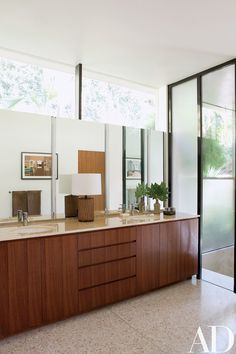 A counter of honey onyx tops walnut cabinetry in the master bath; the sink fittings are by Dornbracht, and the lamp is a Brent Bennett design. Reflected in the mirror are works by Francesca Gabbiani.