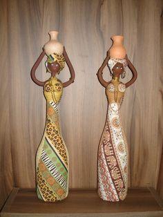 Boneca estilo Africana confeccionada com biscuit e tecidos sobre garrafas de vidro, tendo como adornos, pote de cerâmica e metais diversos.