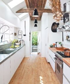 Natural wood is a great flooring option for a modern, white kitchen.