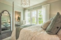 House of Turquoise, white drapes frame the triple window in this bedroom