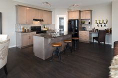 Sierra Showhome in New Brighton featuring light cabinets against a dark hardwood floor and an island with ample sitting room
