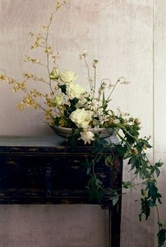 Asymmetrical floral arrangement on a dresser. Looks like a sculpture. Beautiful photograph too.