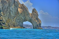 A graceful natural rock formation stands astride the point where the Gulf of California meets the Pacific Ocean