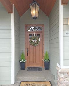 Craftsman lodge entryway with lantern light. Magnolia wreath and greens from symmetrical planters...