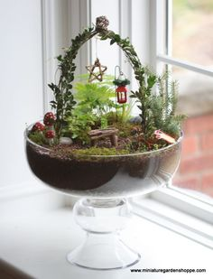 miniature garden example Sometimes subtle is nice. This little fairy garden has a few red accessories that create a holiday feel when combined with the greens of the garden.