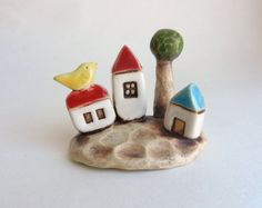 This cute village with a little yellow bird sitting on the roof is hand made out of white clay. The sculpture measures approx. H 2 1/2 x W 3 x D
