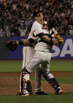6/13/12. MATT CAIN winces in pain as...  Nah, it's just a bad photo.  CAIN and BUSTER POSEY celebrate on the mound moments after the last out in Cain's Perfect Game on 6/13/12. (Photo by Jeff Chiu).