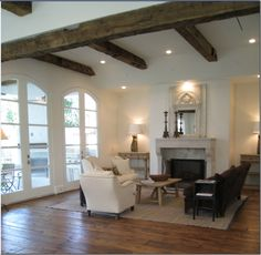 """At the end of the long center hall is the family room on the right and the breakfast room/kitchen on the left. Another trumeau mirror highlights the 18th century """"cheminee"""" taken from a country house in France. Here, Barber paired a barley twist settee with a brown velvet sofa. Two matching wood consoles with pedestal lamps flank the fireplace. The family room is 19' x 19'; antique wood beams run from here into the kitchen."""