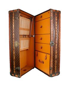 A Louis Vuitton signature wardrobe trunk, early 20th century, conjures up visions of traveling on the QE2. When standing upright, the front opens up into multiple drawers on one side and hanging compartments on the other, monogram at side A.G. New York, with hotel stickers throughout. Stamped: Louis Vuitton/Paris London. 43x21x17 inches.