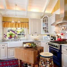 Yellow painted kitchen with high ceilings, apron sink and red accents.