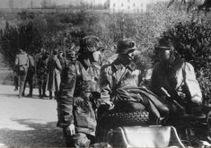 Italy 1944. Members of a unit of the German Polizei in an anti-partisan operation. The Polizei on the left wears a uniform in Italian Telo Mimetico, the remaining two wear the Kradmantel of the first type with the collar in dark blue green cloth. Detail of new tire with center with burr.