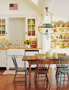 Mismatched chairs, see-through cabinets, wooden floors and warm spaces = love