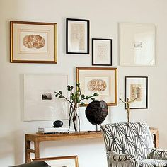 Lindsey Meadows - entrances/foyers - white walls, white wall color, slim wooden console table, wooden console table, black framed art print, gold framed art print, white framed art print, gallery wall, gallery wall over console table, stacked books, glass vase, branches, turtle shell, tortoise shell, gold sculpture, black and white armchair, graphic black and white armchair, armchair upholstered in Kelly Wearstler Katana Fabric, Kelly Wearstler Katana Fabric, art over console table,