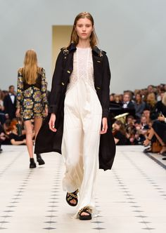 Black lightweight silk wool trench coat with regimental metallic braiding and white silk crepe and lace long dress. Discover the collection at Burberry.com