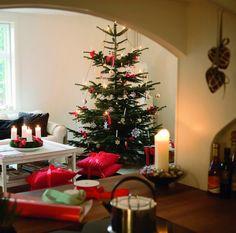 Stuen i al sin pragt - klædt på til højtiden. Juletræet har fået en central placering i hjemmet, her pyntet med nyt og gammelt pynt. De røde puder på gulvet bruges kun i julemåneden. Her fungerer de som siddepuder med store sløjfer bundet omkring. Puderne er fra Ilse Jacobsens forretning. - Klassisk jul hos Ilse Jacobsen - Bolig Magasinet