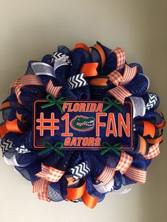 "Florida Gators Mesh Wreath. This wreath is made on a rich navy blue mesh with foil highlights. It features a Florida Gators #1 Fan centerpiece surrounded by six different high quality, navy blue, orange and white wired ribbons. This wreath measures approximately 22""-23"" in diameter. What a great way to show your support for your favorite team and to welcome your family and friends to your home."