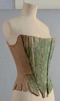 Auction House Coutau-Bégarie - Corps à baleines, vers 1760, en toile de lin bis et damas bicolore vert à dessin darabesques de fleurs et oiseaux, piqûres rectilignes soulignant les baleines. Découpe crantée en pointes devant et basques étroites. Laçage à oeillets dans le dos, (doublure déposée, usures).