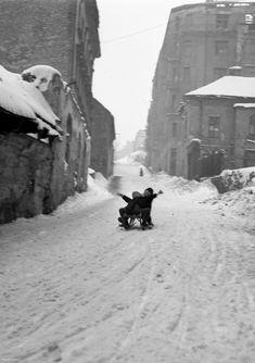 """Valószínűleg a Fiath János utca úttestén 1946-ban szánkózó gyerekek szabálysértést követnek el, ugyanis akkoriban nem lehetett Budapesten akárhol csúszkálni. """"Szánkázni és síelni a fővárosi tanács rendelkezése alapján csak a kijelölt helyeken szabad. A Gellért hegyen csak a déli lejtőn, a Ménesi-út és a Villányi-út közötti magánterületen szabad szánkózni, az Összes kocsival járható utón azonban tilos a szánkózás. Csak a gyermekek szánkózhatnak az Orbánhegyi-út, Istvánliegyi-út, Nárcisz-utca…"""