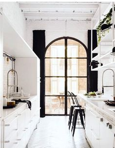 I should like this. I don't. is there too much black at one end of the room? Does it require balance ? Is it the curtains ? Discuss. cool white contemporary kitchen with arched window and black drapes