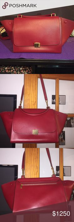 Authentic Cēline Large Red Trapeze. Authentic Céline Large Leather Trapeze Bag with gold-tone hardware, detachable flat shoulder strap, rolled handle, snap closures, red suede lining, dual pockets at interior wall and fold-over flap featuring flip-lock closure at front. **WORN TWICE. Minimal scratches. It's leather is unique: any incidental tonal variations, marks, or veins are natural features, and should NOT be considered as imperfections.** Celine Bags Shoulder Bags