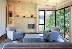 Contemporary White Living Room with Blue Accents: A simple, unique and informal fireplace takes center stage in this contemporary living room.
