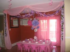 I like how they made a partition using plastic table cloths and the silk flowers.  Darker theme for a scary tale party.