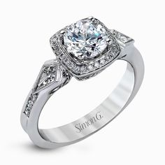 The romantic setting of this vintage-inspired white gold ring highlights an eye-catching halo and .20 ctw of glistening round cut white diamonds and .23 ctw of kite shaped diamonds.