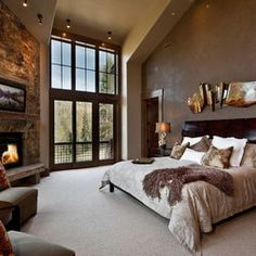 Master Bedroom. King bed with cream comforter, taupe-brown throw, white shams, brown and taupe decorator pillows, and dark cream sleep pillows, wooden headboard, fireplace, chairs, full-wall windows with French doors and outlook area. Yes and yes. Perfect for a Colorado home
