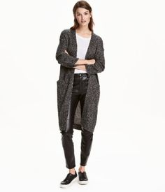 Black/white melange. Long cardigan in a soft, chunky knit with dropped shoulders, front pockets, and no buttons.