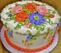 Buttercream flowers in peach, coral, lavender. on 2-layer cake.