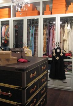 Hermes boxes provide color in this dressing room w/glass front cabinets & a gorgeous steam trunk type center island