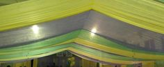 A school decorated the gym with this on the ceiling. Great look! Looks like table clothes draped over a fish wire line & pinned on both sides.