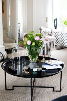 Black coffee table decorated with fresh flowers, beautiful living room