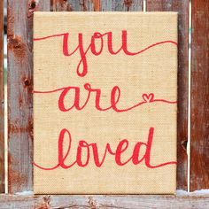 "You are loved. Such a simple statement with a powerful punch.Tell your valentine how you feel this Valentine's Day with an 11x14 inch burlap sign. ""You are loved"" is hand lettered in red paint on burlap wrapped around a sturdy wooden frame. It is ready to hang, but looks great on a mantle or shelf as well.Give this sign AS a valentine, or use it in your Valentine's Day decor. Either way, it is sure to bring lots of love.Feel free to ask if you have any question..."