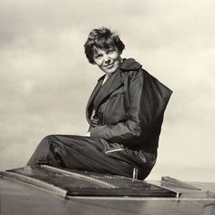 Amelia Earhart sitting on her plane, ca. 1935.
