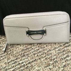 Grey Michael Kors Wallet Grey MK wallet, practically brand new. Used only a few times. All leather. No scratches or markings. Perfect condition! 8 slots for cards with 2 slots for cash and also a zipper for change! Slot is also on the outside back of the wallet. Michael Kors Bags Wallets
